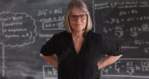Foto  Old senior woman teacher with serious attitude posing in front of chalkboard