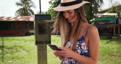 Fotografie, Obraz Millennial girl in her 20s text messaging on cellphone while in Costa Rica