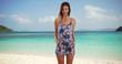 Portrait of pretty brunette in romper posing for camera outside on serene beach