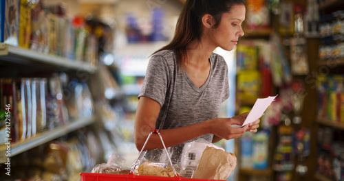 Photo Pretty female customer carrying grocery basket looking for item in store aisle