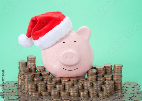 Photo  Pink piggy bank wearing a Santa hat smiling facing viewer surrounded by stacks of coins, green background