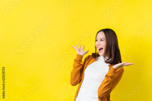 Obraz na plátně Asian girl is surprised she is excited.Yellow background studio