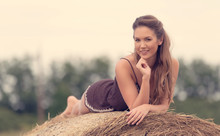 Beautiful Woman Relaxing On Hay Bale