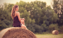 Beautiful Woman Relaxing On Hay Bale