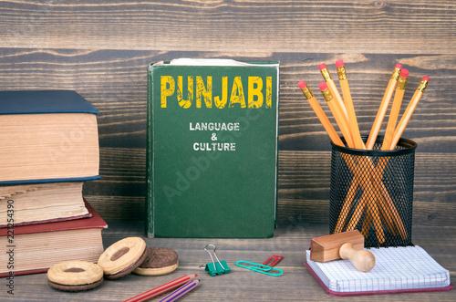 Fotografia, Obraz  Punjabi language and culture concept. Book on a wooden background