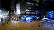 Hectic City Nightlife. Taxi Cabs, Double Deck Buses, Trams Crossing A Crossroad In The Central District. People Fast Walking Pedestrian Crossing. Time Lapse With Tilt-shift Effect