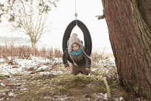 Cute Girl Playing In Tire Swing In Snowy Yard