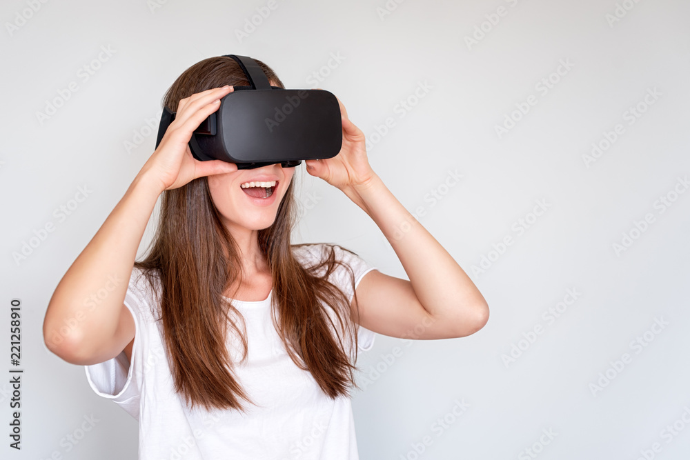 Fototapeta Smiling positive woman wearing virtual reality goggles headset, vr box. Connection, technology, new generation, progress concept. Girl trying to touch objects in virtual reality. Studio shot on gray