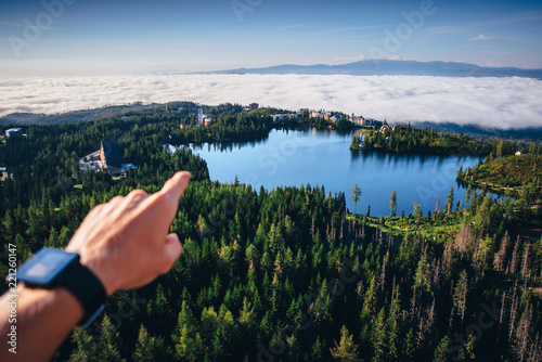 Spoed Foto op Canvas Natuur Hand pointing to the beautiful nature on blue lake and mist in the valley