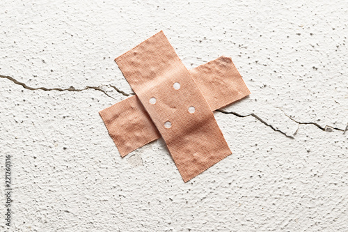 Photo band-aid plaster in cross shape on a crack in the wall, concept for botched cons