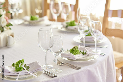 beautifully decorated festive table with plates and glasses and a bouquet of flowers in a restaurant