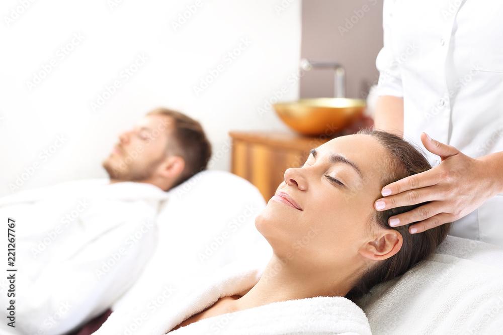 Fototapeta Masaż twarzy dla dwojga. Kobieta i mężczyzna razem na zabiegu pielęgnacyjnym w gabinecie spa.