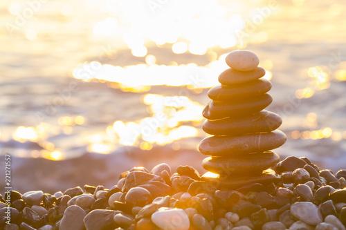Fotografía  Pyramid of pebbles at sea in sunrise