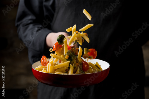 Leinwand Poster Cropped view of chef cooking Italian pasta with cheese, vegetables and egg yolk on hot pan flying