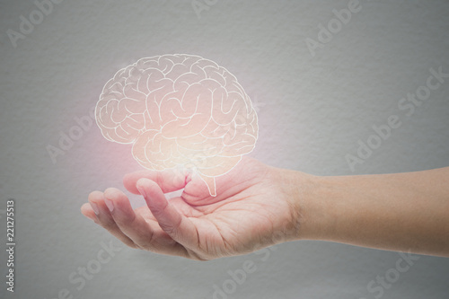 Obraz Man holding brain illustration against gray wall background. Concept with mental health protection and care. - fototapety do salonu