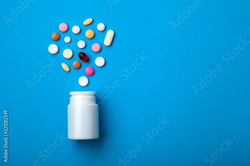 Obraz Pills spilling out of white plastic pill bottle on blue background. Top view with copy space for text, medicine drugstore concept. - fototapety do salonu
