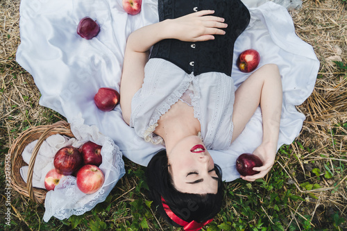 Fotomural Snow White is laying in the floor, surrounded by red apples