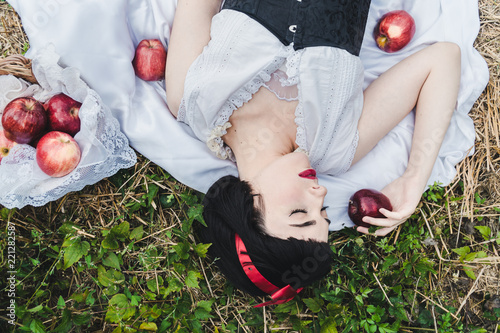 Photo Snow White is laying in the floor, surrounded by red apples