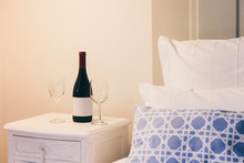 Luxury Bedroom With Bottle Of Red Wine And Glasses. Hotel Interior