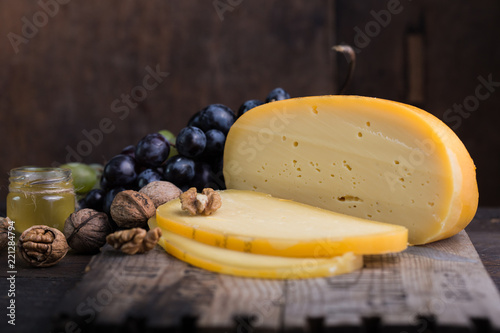 Dutch hard cheese Maasdam or Emmentaler, cheese with grape, nut , honey and white hard goat cheese . Whole cheese, slisec of cheese. cheese with honey fruit and grape