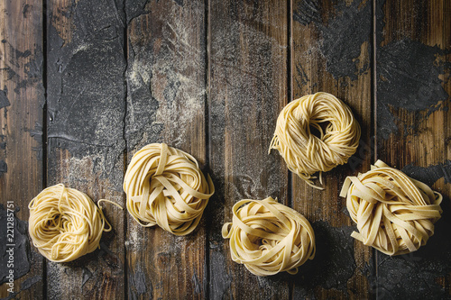 Obraz na płótnie Variety of italian homemade raw uncooked pasta spaghetti and tagliatelle with semolina flour over dark plank texture wooden table