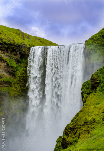 Poster Watervallen Beautiful Iceland Waterfall.Fast running river. Rugged volcanic rock cliffs against blue skies with low clouds. Green moss and grass covered rock formation.