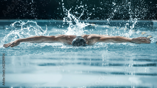 Fotografía  The dynamic and fit swimmer in cap breathing performing the butterfly stroke at pool