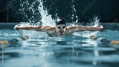 Photo The dynamic and fit swimmer in cap breathing performing the butterfly stroke at pool