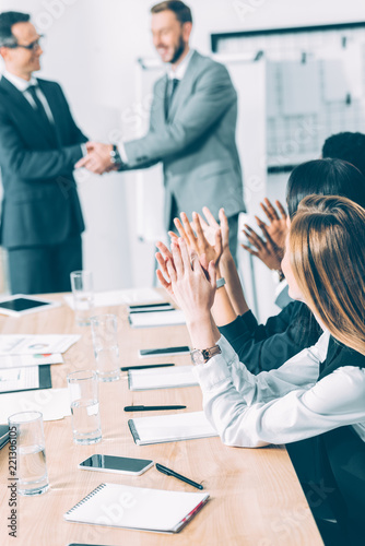 boss shaking hand of manager while colleagues clapping in conference hall Canvas Print