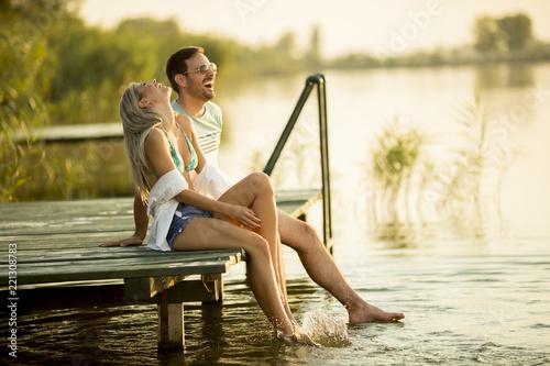 Fotografia  Romantic couple sitting on the wooden pier on the lake