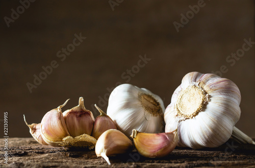 Fotomural  Closeup garlic on wooden texture on for cooking on dark background