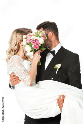 young newlyweds covering faces with bridal bouquet while groom carrying bride is Fototapeta