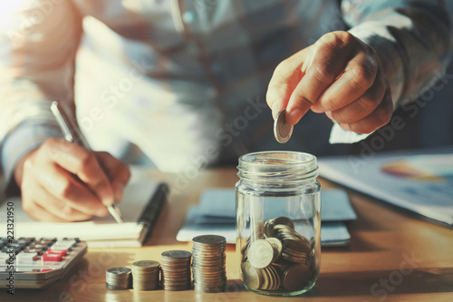 Fototapeta businessman saving money concept. hand holding coins putting in jug glass obraz