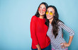 canvas print picture - Two beautiful brunette women in sunglasses posing and hugging over blue background
