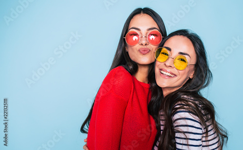 Obraz Friends forever. Two cute lovely girl friends in sunglasses posing with smile on blue background - fototapety do salonu
