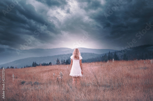 Back view of a blonde woman in white dress standing on the top of the hill with dark stormy sky background. Color tone filter effect used.
