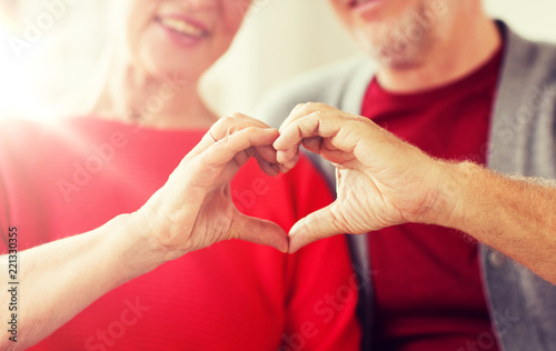 Fototapeta relationships, love and old people concept - close up of senior couple showing hand heart gesture obraz
