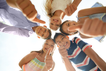 Fototapeta childhood, friendship and gesture concept - group of smiling happy children showing thumbs up in circle