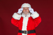 Christmas. Serious Santa Claus In White Gloves Adjusts Her Glasses And Stares Into The Camera. Isolated On Red Background.