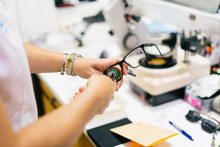 Female Optician Measuring And Preparing Glasses On The Latest Digital Device In Optical Store. Professional Ophthalmology Instrument In Clinic Office And Optics
