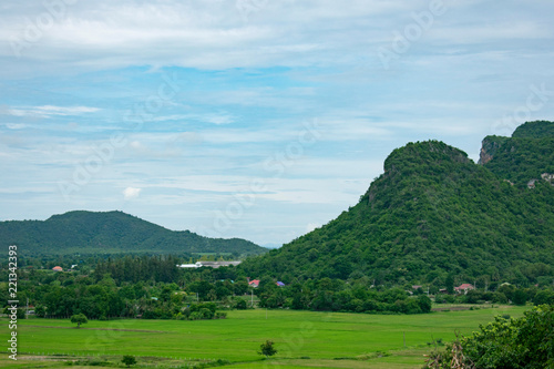 landscape with green field, mountains and blue sky