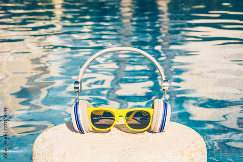 Photo sur Toile Magasin de musique Attributes of summer vacation - sunglasses and headphones - on the background of the pool