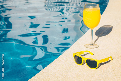 Fotografia Sunglasses and a glass of juice on the poolside - girl on vacation
