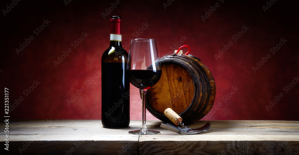 Red wine glass with bottle and small barrel