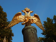 The Golden Figure Of The Two-headed Eagle On The Fence Of The Fence Against The Sky And Trees