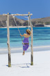 Woman on swing on beach, Kuta, Lombok, Indonesia
