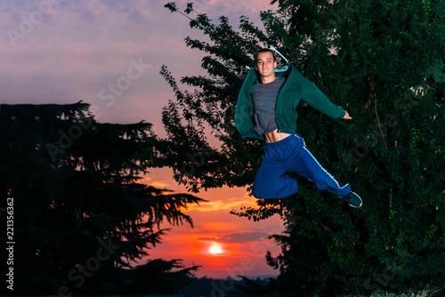Poster Feeën en elfen Man outdoors practicing parkour. Young parkour man while jumping in park on a sunrise