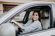 Businesswoman sitting in drivers seat in her car while driving in the street