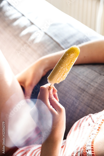 Carefree woman chilling on sofa in daylight and eating ice-cream on stick in sunlight with sunflare sunlight