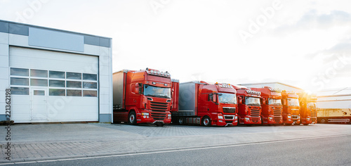 Fototapeta View of squadron group of new red cargo trucks parked in a row near warehouse bu